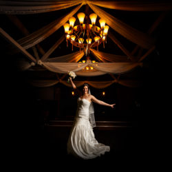 Bride under chandelier striking a pose waving her bouquet above her head at Bartle Hall.