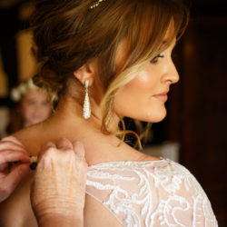 Bride during bridal prep looking to the right whilst her mother fastens her button on her wedding dress.