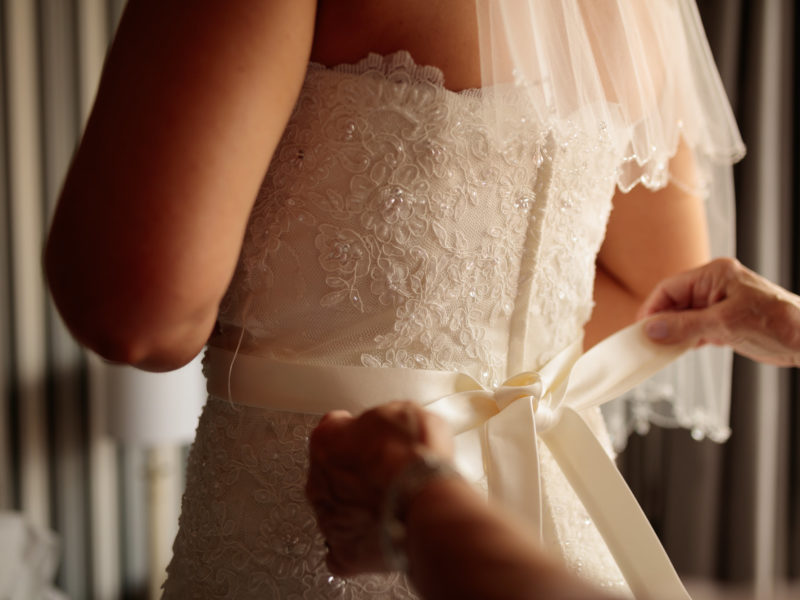 A rear shot of the bride dress with her mother tying her white satin bow.