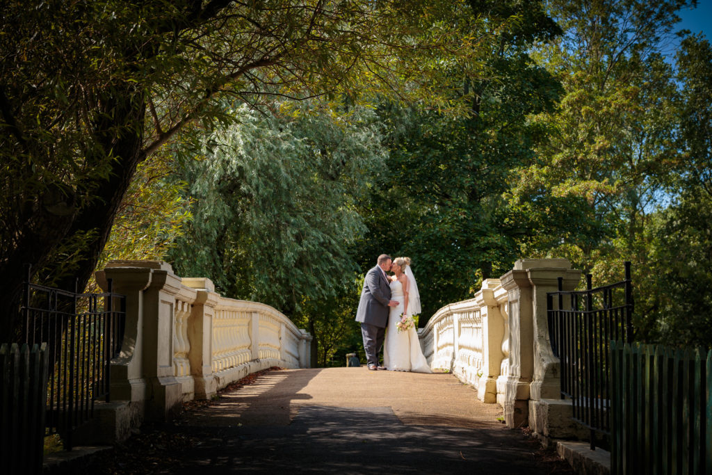Bride and Groom are captured standing on a bridge kissing.The couple are surrounded by trees at Stanley Park,Blackpool.