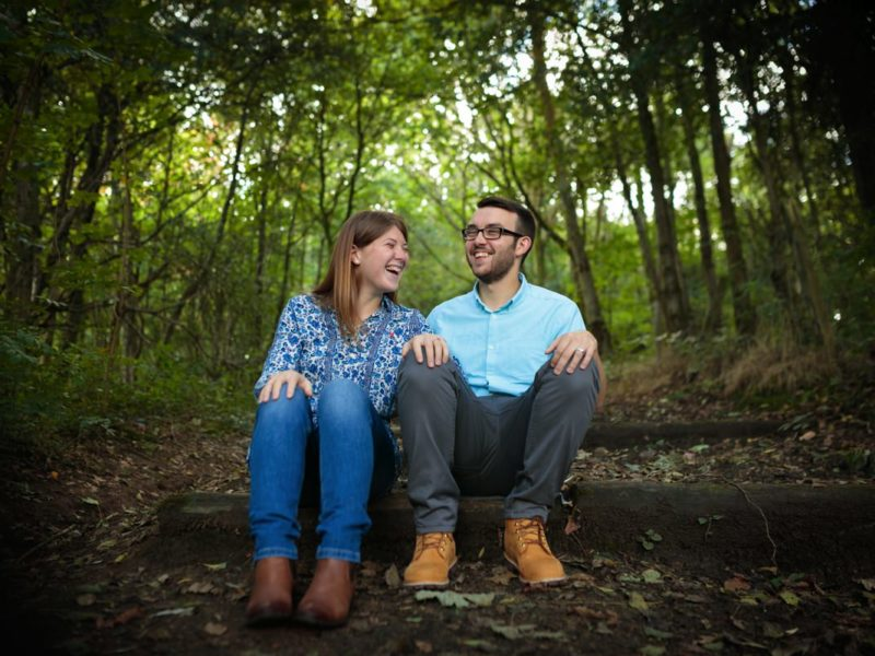 newly engaged couple during their pre-wedding photo shoot captured sat on wooden steps in woodland.Both the bride and groom-to-be are laughing with their hands on their knees at Reddish Vale Country Prk.