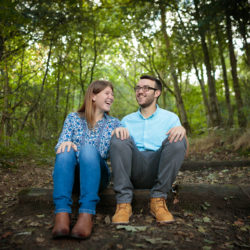 Newly engaged couple sat on a wooden step on a woodland path with their hands on their knees laughing ay Reddish Vale Country Park.