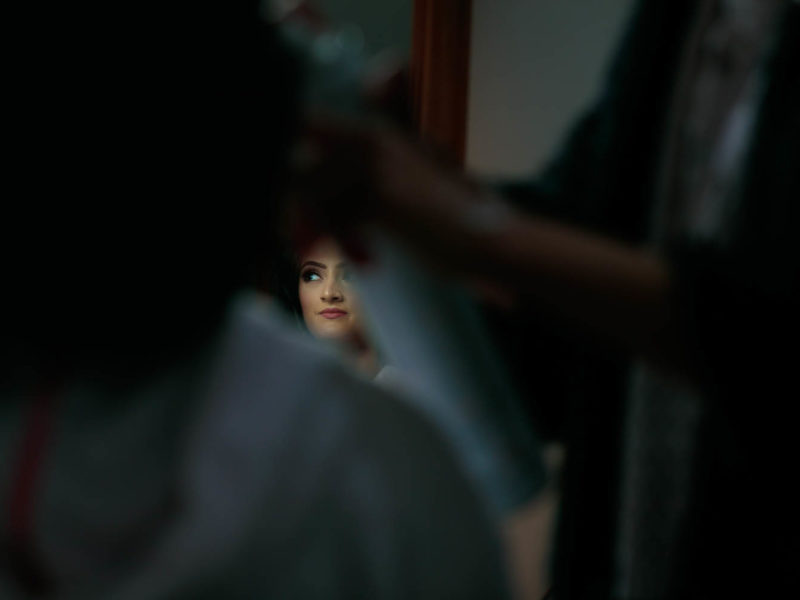 Muslim Bride during her Bridal prep. Bride is looking to her left whilst her Make-up-Artist sprays her hair with hairspray.Bride's reflection is captured in the mirror in Preston