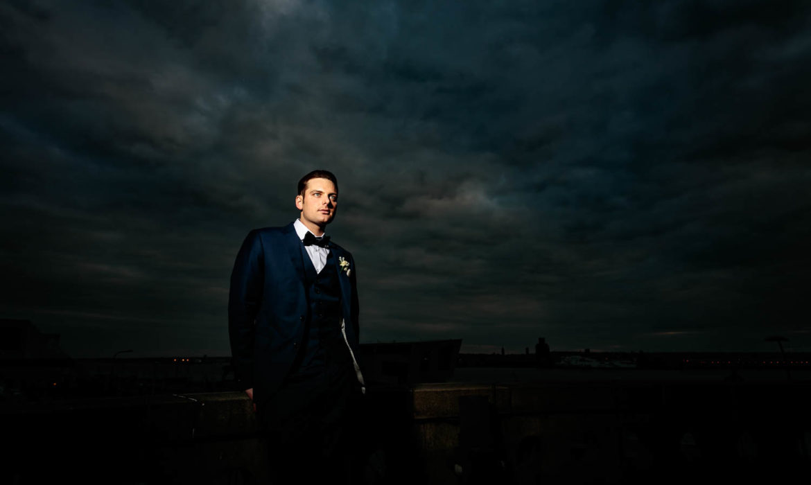 Groom stood on the top of the Liver Building , with a dark sky behind him at The Liver Building,Liverpool