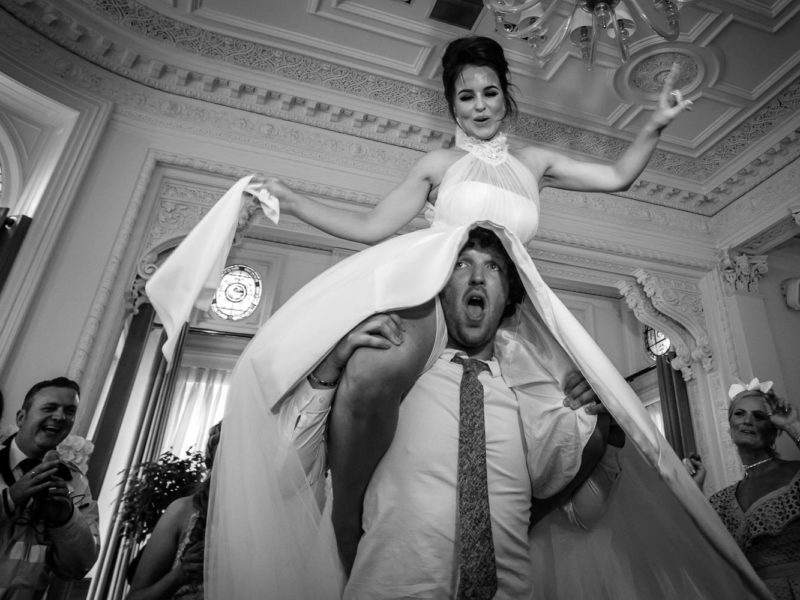 Black and white image of the Bride sat on the Groom's shoulders at Doubletree by Hilton.
