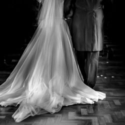 Bride and her father from behind,which captures her cathedral wedding veil in Burnley.