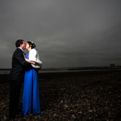Bride and Groom kissing on the beach at Morecambe.