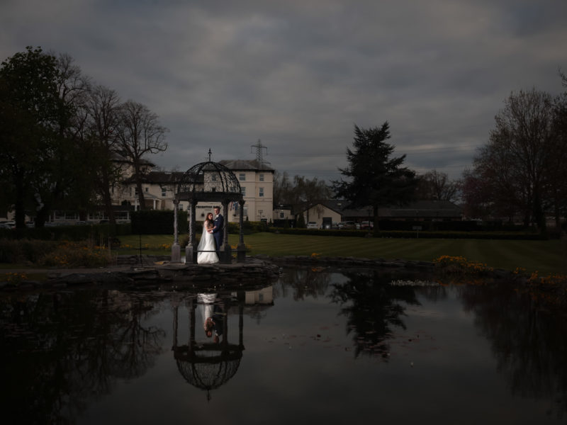 Bride and Groom stood inside a Pagoda in the hotel grounds,with their reflection in the lake at Thornton Hall.