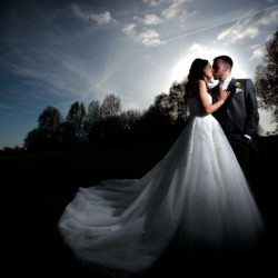 Bride and Groom kissing,surrounded by trees with aircraft trails in the blue sky above at Fairways Lodge,Manchester.