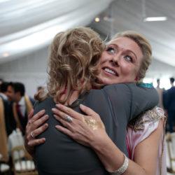 Bridesmaid hugs a guest at a Hindu/Christian Fusion Wedding at Heaton House Farm.