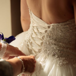 Bride having the back of her dress laced up by her mother.