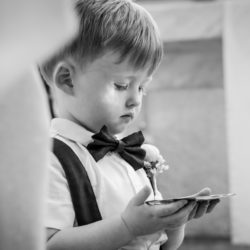 Young Son of Bride and Groom holding onto the the wedding rings on a small silver tray St.Margaret Marys Parish House.