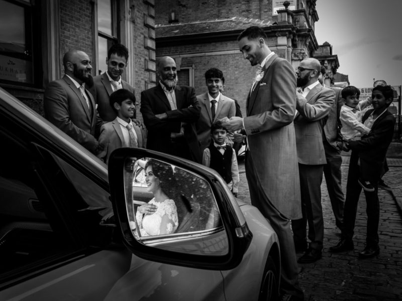 Black and white image of Muslim Bride sat in the car with her reflection captured in the wing mirror. Muslim Groom is pretending to pay the dowry to Bride's family at Tipu Sultan Majestic Dining.