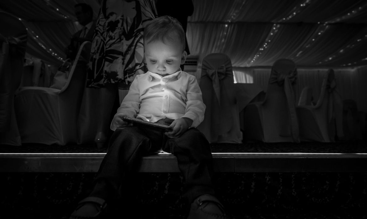 Black and white image of Bride and Grooms son sat on a step staring down into his ipad at Pavillion on the Prom.