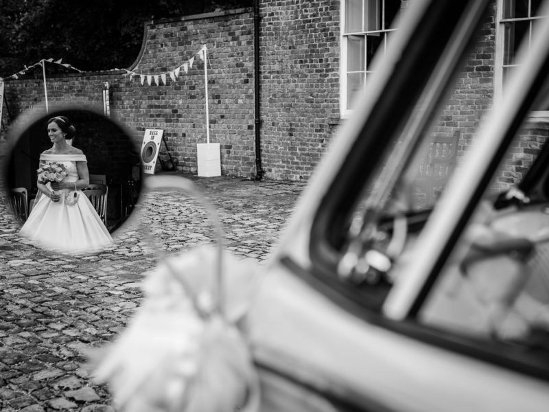 Bride captured in the wing mirror of the bridal car at Meols Hall.
