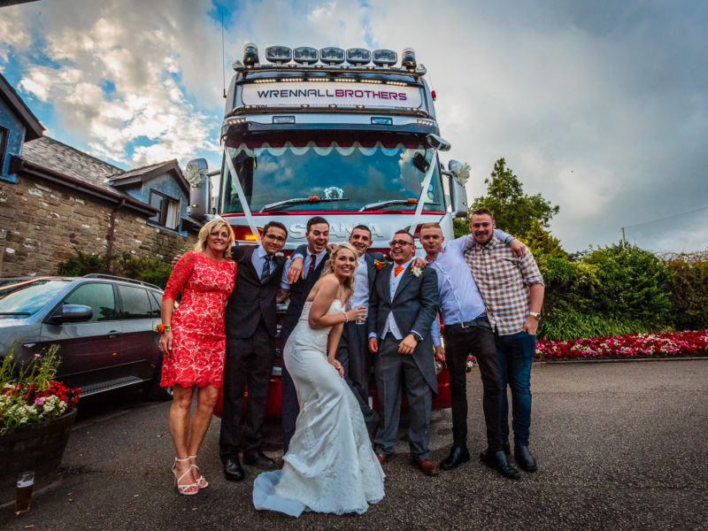 Bride,Groom and several wedding guests captured in the hotel grounds in front of a HGV lorry used for the wedding party at Garstang Country Hotel and Golf Club.