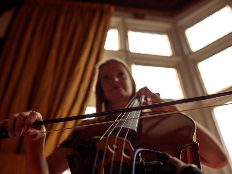 Lady playing a Cello in front of a large bay window at Delemere Events.