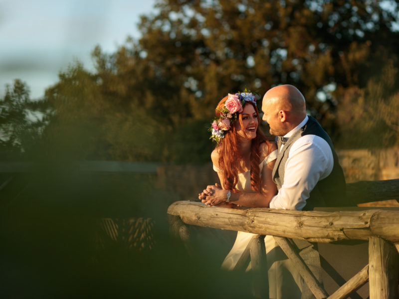 Bride and Groom stare at each whilst laughing, leaning against a wooden fence post,with the sunlight on their faces at Chester Zoo.