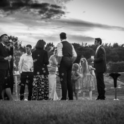 Black and white image of wedding guests stood in the venue grounds blowing bubbles at Delemere Events.