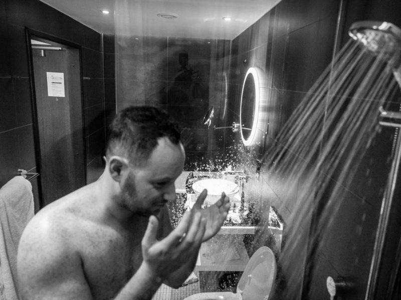 Black and white image of Groom in his hotel bathroom about to get into the shower at The Palm House in Sefton Park.