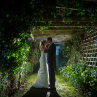 Bride and Groom facing each other, kissing in a wooden tunnel of Ivy and Evergreens at Garstang Country Hotel and Golf Club.
