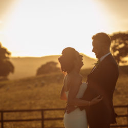 Bride and Groom stood in a field, with hills and the sun going down in the background at Heaton House Farm.