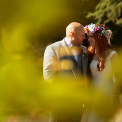 Bride and Groom looking at each other surrounded by greenery at Chester Zoo.