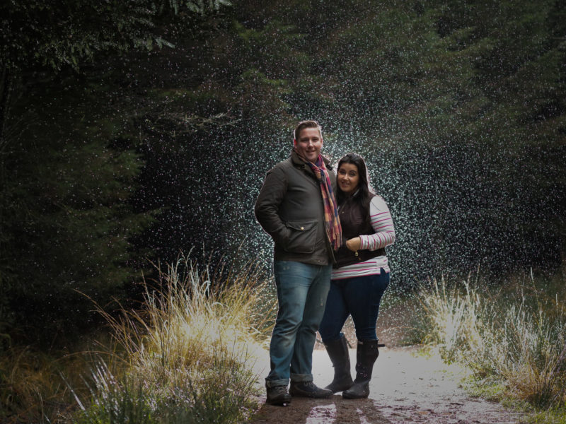 Engaged couple having a Pre Wedding shoot in the rain surrounded by trees at Beacon Fell Country Park.