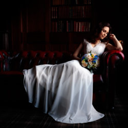 Bride lying on a red Chesterfield sofa, looking to the right holding her bouquet at Ashfield House,Wigan.