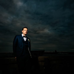 Groom stood on a building rooftop, with a cloudy dark sky behind him at The Liver Buildings,Liverpool.