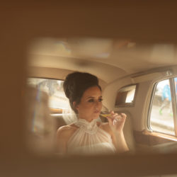Bride sipping champagne in the backseat of her wedding car.Image captured in the drivers rear view mirror.