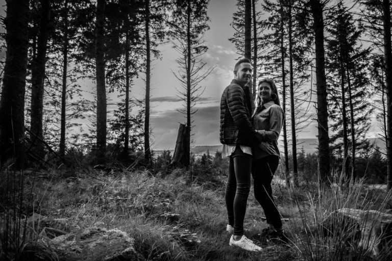 Black and white image of newly engaged couple during their pre-wedding photo shoot. Bride and Groom to be are stood in a woodland clearing,stood facing each other and looking down into the camera at Beacon Fell Country Park