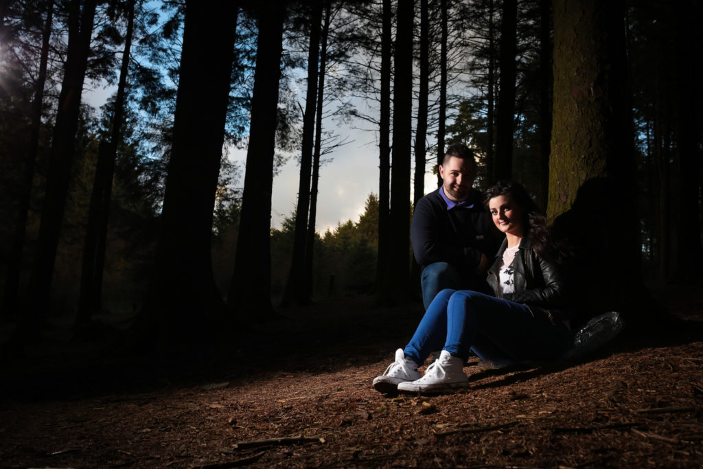 Newly engaged couple during their pre-wedding shoot captured in a forest.Bride-to-be is sat on the floor with her back against a tree and her groom-to-be is knelt behind her at Beacon Fell Country Park.