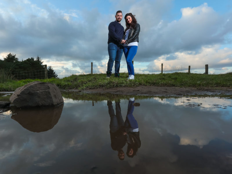 Newly engaged couple during their pre-wedding photo shoot.Bride and groom-to-be are captured behind a stream and their reflections can be seen in the water at Beacon Fell Country Park.