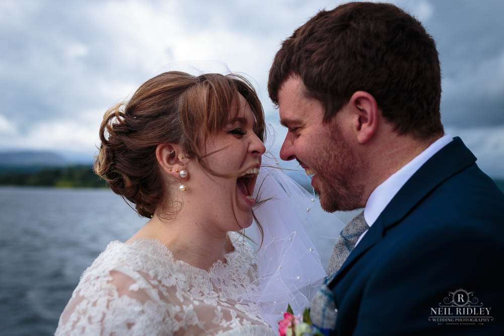 Bride and Groom laughing together on a Lake District cruise around Lake Windermere