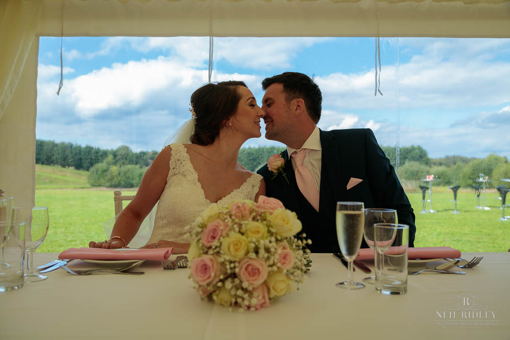 Bride and Groom kissing at the top table at Delemere Events.