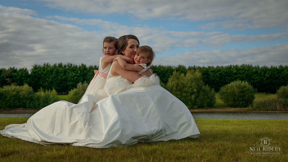 Bride sitting on the ground with her two daughters at Delemere Events