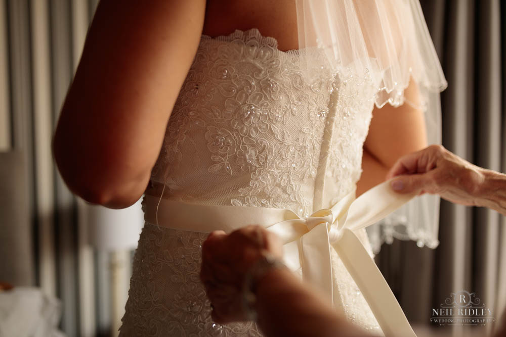 Brides dress being fastened by the Mother of The Bride during Bridal Prep.