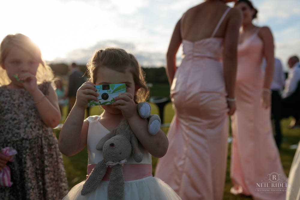 Young Bridesmais taking a photo with her toy Bunny.