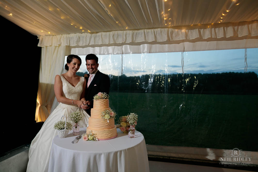Bride and Groom cutting the cake at Delemere Events.