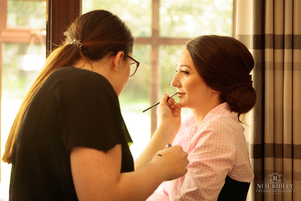 Bridal Prep, bride having lipstick applied by make up artist prior to her traditional church wedding.