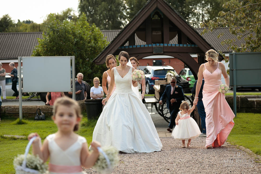 Bride walking on the Church path for her traditional church wedding.