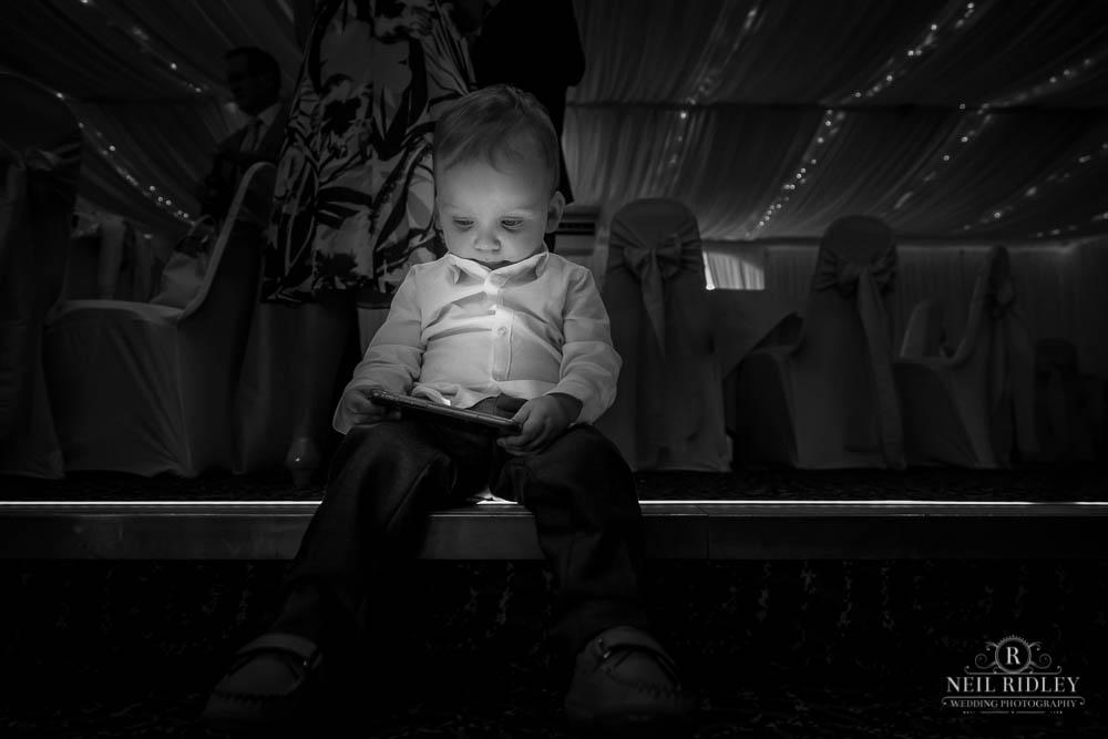 Little boy on dancefloor with ipad.