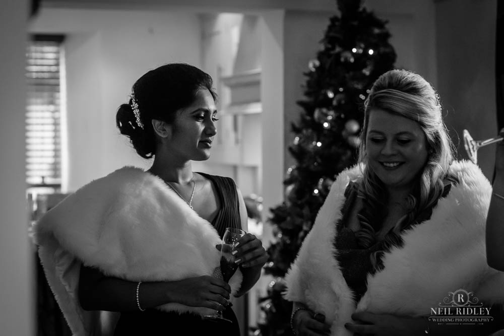 Black and white photo of bridesmaids stood next to the chriistmas tree