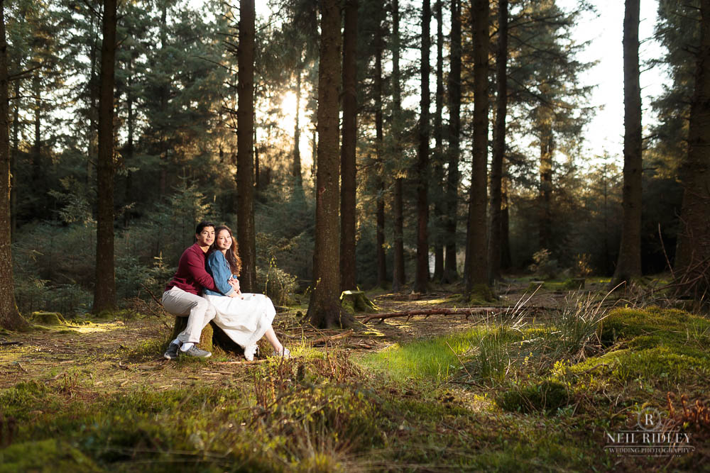 Young couple sitting in a forest clearing with the sun setting behind them