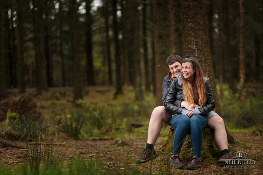 Lancashire Pre Wedding at Beacon Fell, a young couple sat on a log