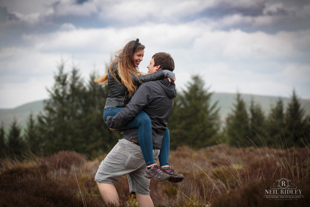 Lancashire Pre Wedding at Beacon Fell, a young man lifting a young lady