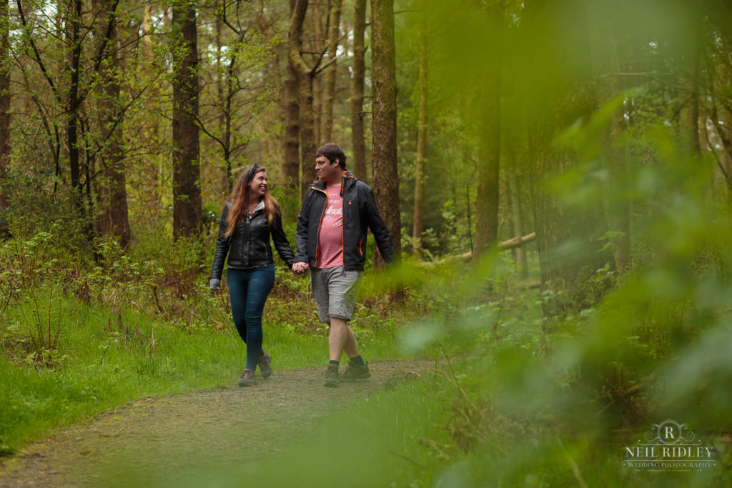Lancashire Pre Wedding at Beacon Fell, a young couple walk through the woods hand in hand