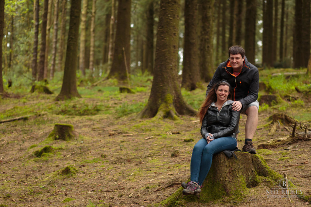 Lancashire Pre Wedding at Beacon Fell, a young couple pose by a tree stump