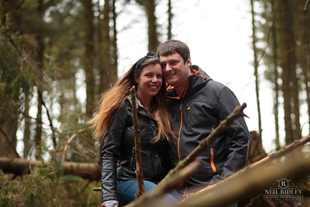 Lancashire Pre Wedding at Beacon Fell, a young couple pose cheek to cheek in the forest